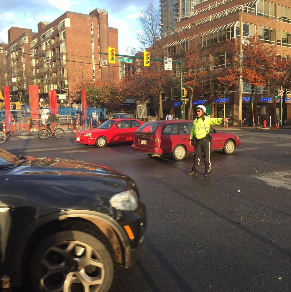 Un civil gère la circulation sur le chantier d'une rue achalandée du sud du centre-ville de Vancouver.