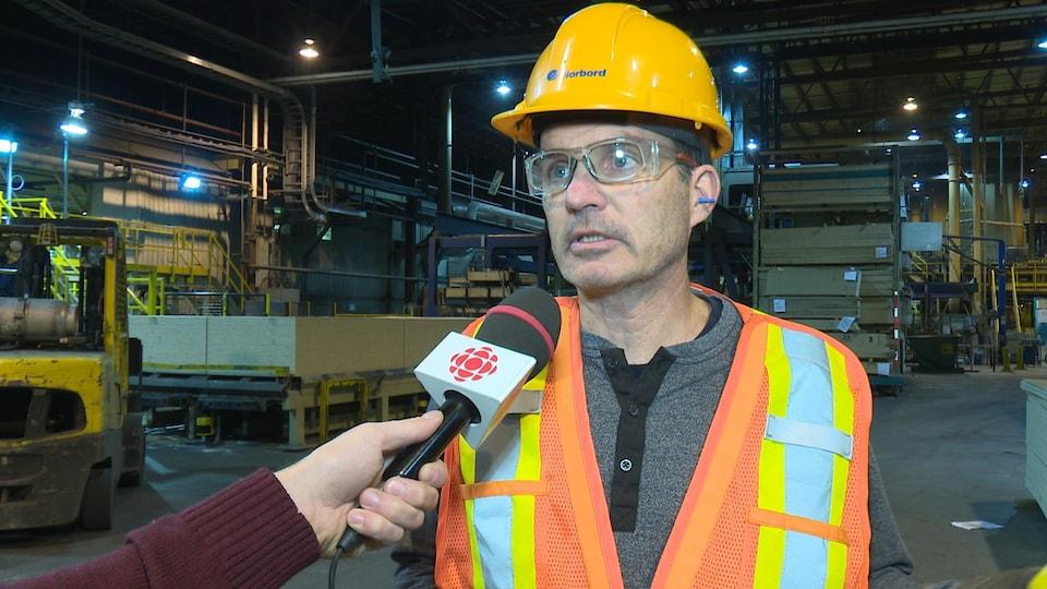 Un homme portant un casque de Norbord et des lunettes de protection accorde une entrevue à un journaliste hors-champ.