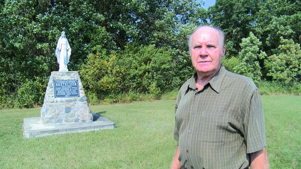 Clément Bretecher devant le monument commémoratif des premiers pionniers du petit village Toutes Aides, au Manitoba.