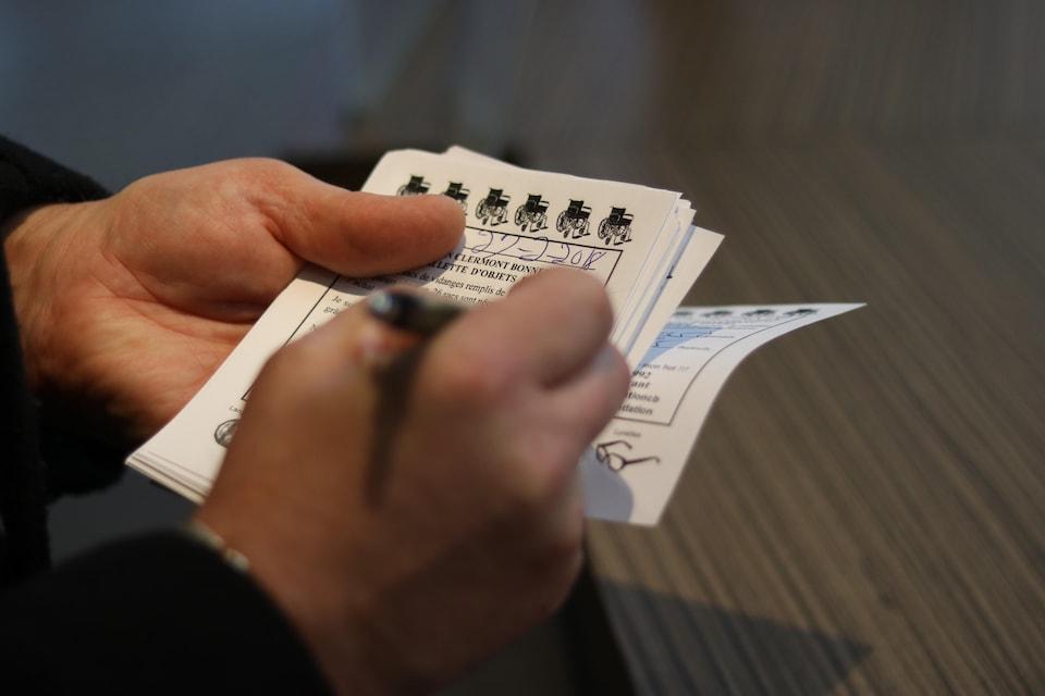 Les mains de Clermont Bonnenfant inscrivant des informations sur un bout de papier.