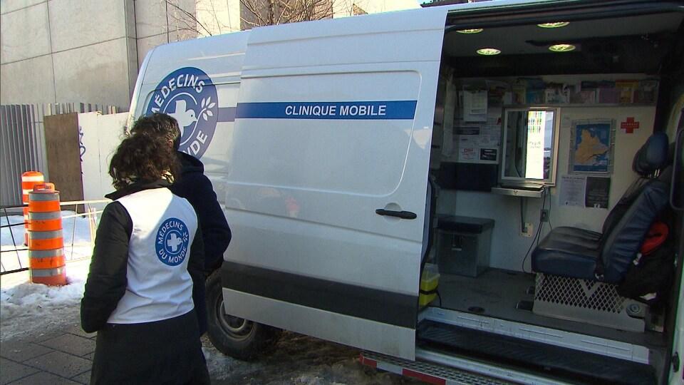 Des bénévoles de Médecins du monde Canada discutent à côté de la camionnette qui fait office de clinique mobile.