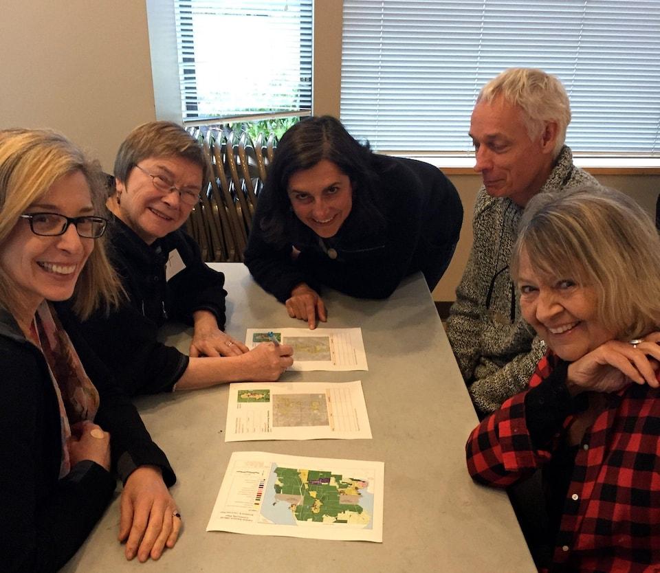 Cinq personnes sont attablées autour de plans immobiliers.
