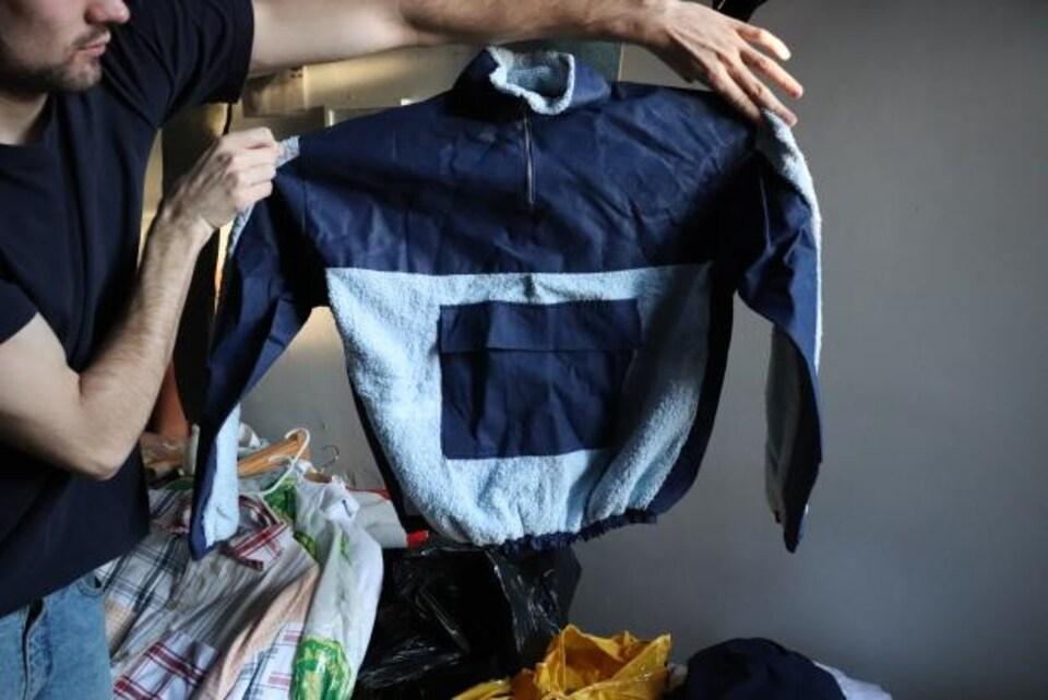 Un homme montre un chandail bleu.