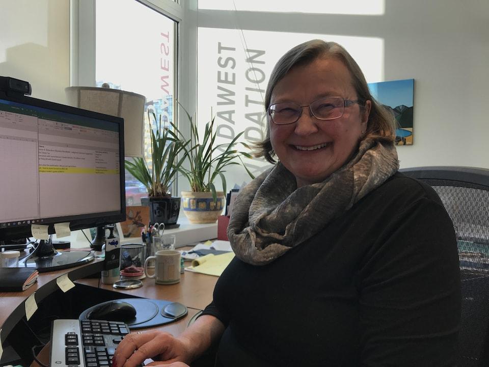 Colleen Collins, souriante devant son ordinateur.