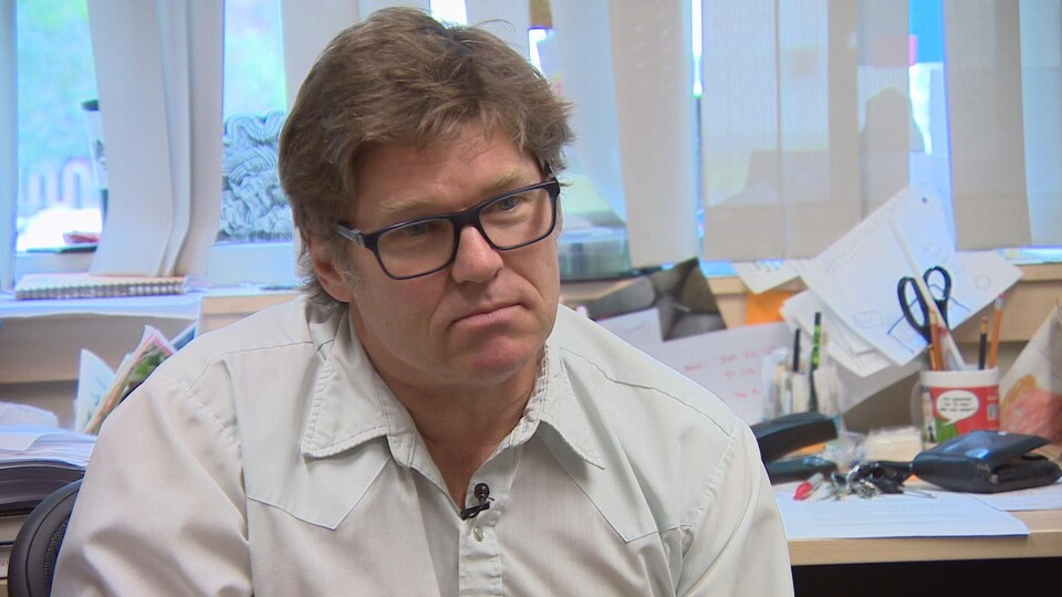 James Daschuk parle à la caméra assis devant un bureau de travail couvert de documents et d'objets variés.