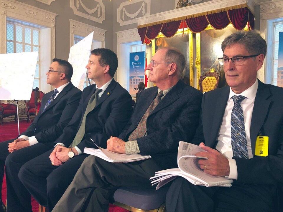 Les quatre hommes sont assis l'un à côté de l'autre