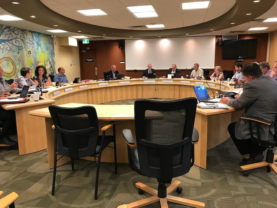 Autour d'une table ronde en bois clair, plusieurs personnes sont assises et examinent leurs ordinateurs portables placés devant elles.