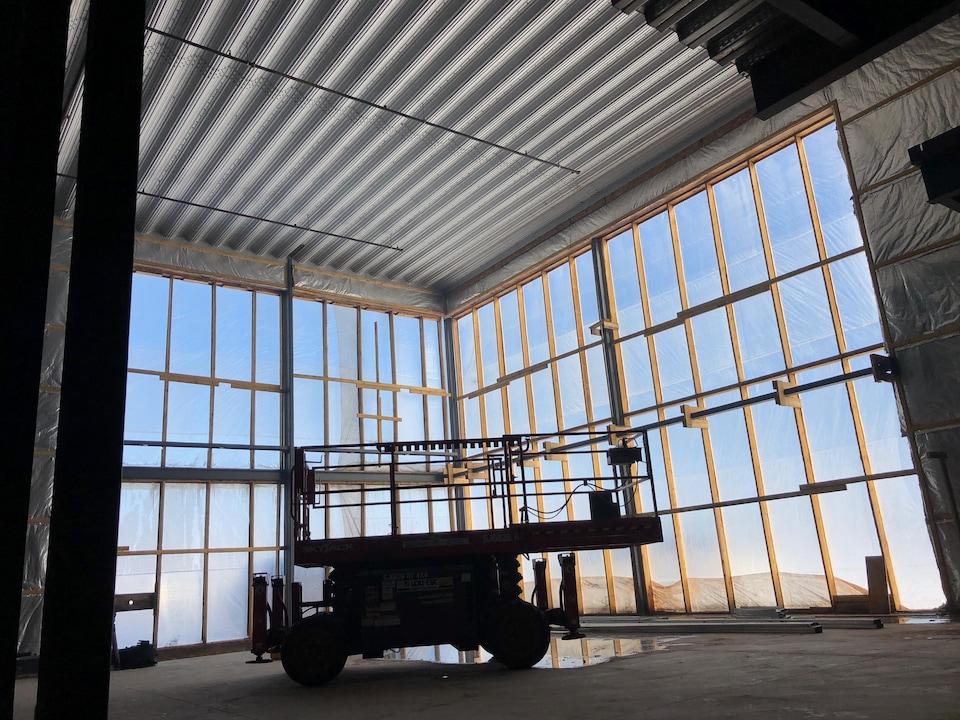 Grandes fenêtres vitrées. Une pièce d'équipement de construction est au centre de la pièce.
