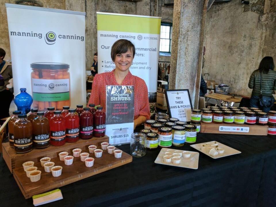 Christine Manning sur un stand d'exposition présente ses produits.