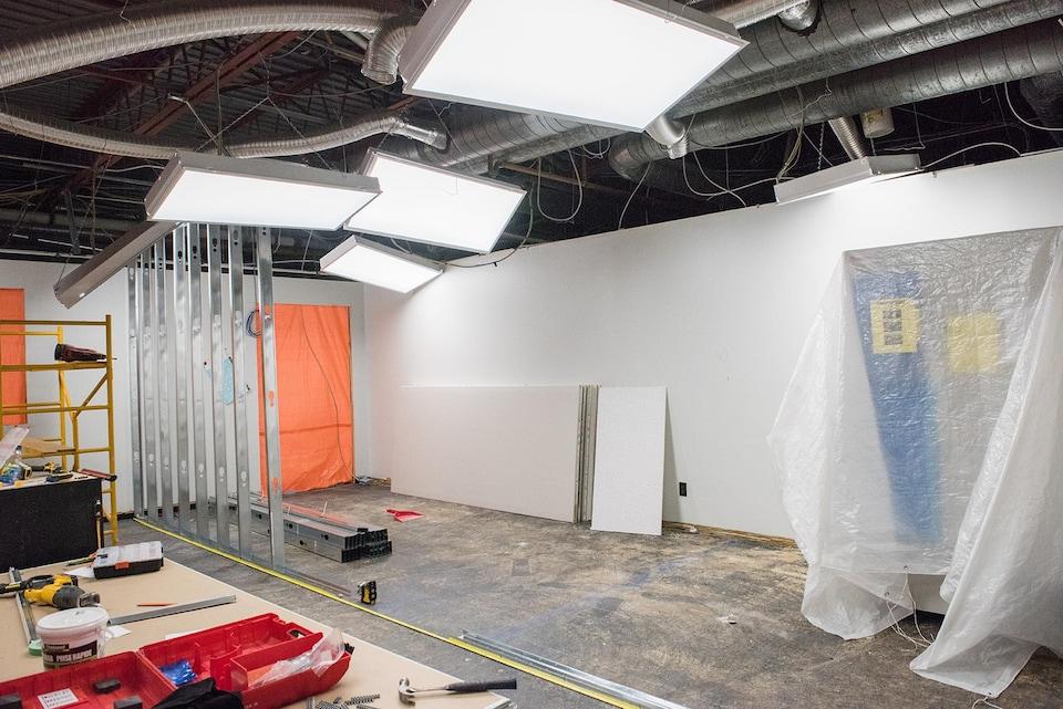 Le laboratoire n'est pour le moment qu'un chantier de construction où l'on aperçoit des outils sur une table et la charpente inachevée d'un mur intérieur.