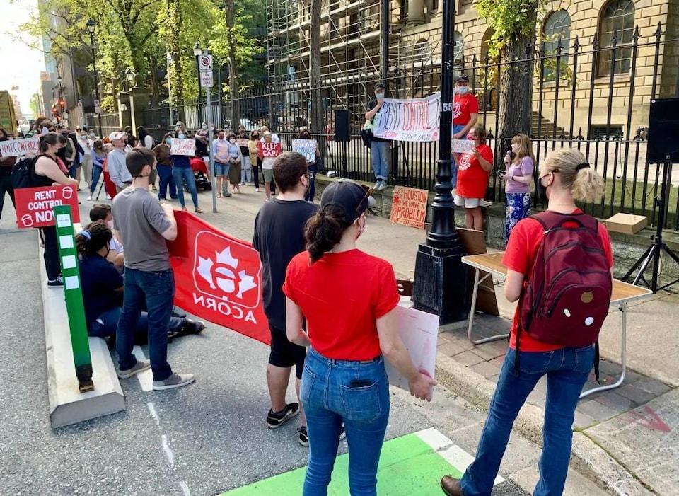 Une personne prend la parole pendant que des manifestants exhibent des banderoles et des affiches.