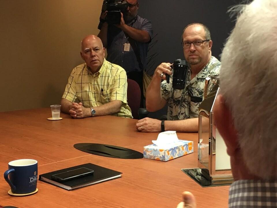 David Coon écoute deux intervenants assis à une table avec lui