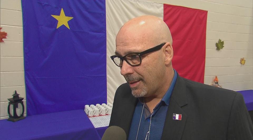 Aubrey Cormier en entrevue, devant un drapeau acadien