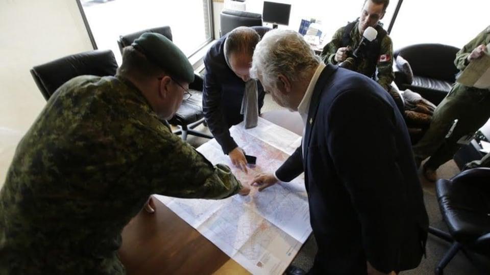 Le premier ministre Philippe Couillard discute avec des membres des Forces armées canadiennes déployés pour aider avec les inondations.