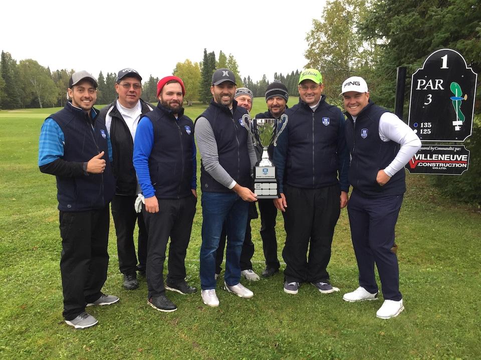 Une équipe de golf avec une coupe.