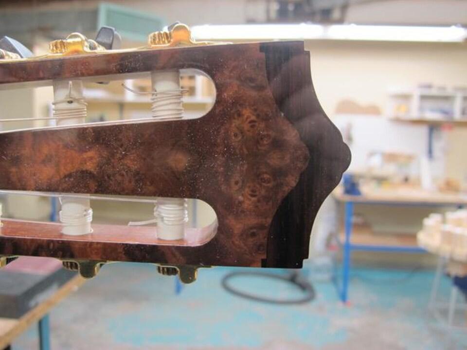 Une couronne de bois dense est placée à l'extrémité de la tête de la guitare pour en changer la résonance.