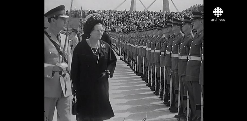 La reine Juliana, accompagnée d'un soldat, se promène devant la garde.