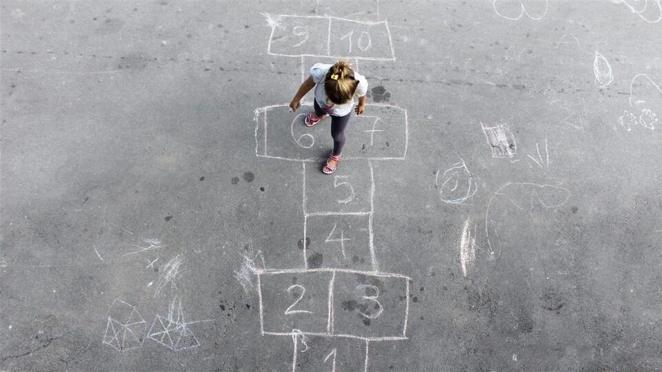 Une fillette joue à la marelle.