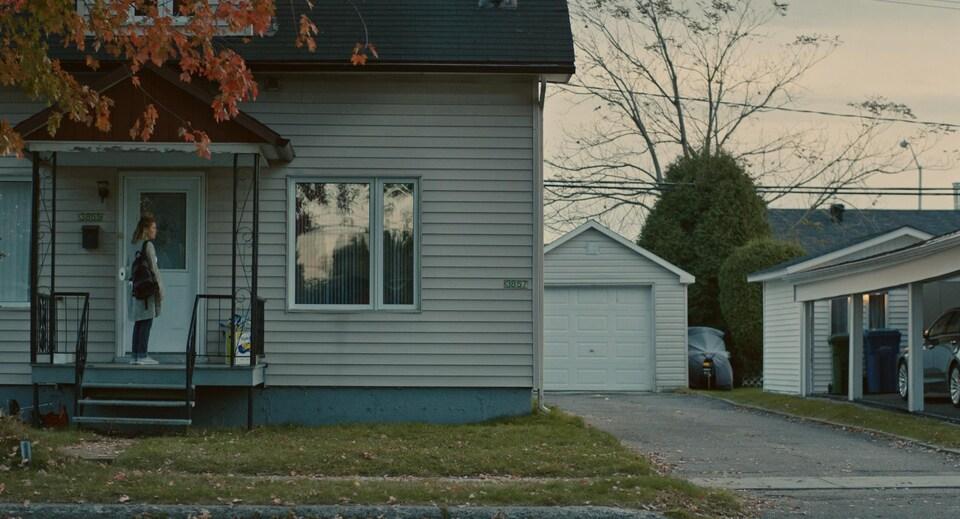 Une femme sur un balcon devant une maison