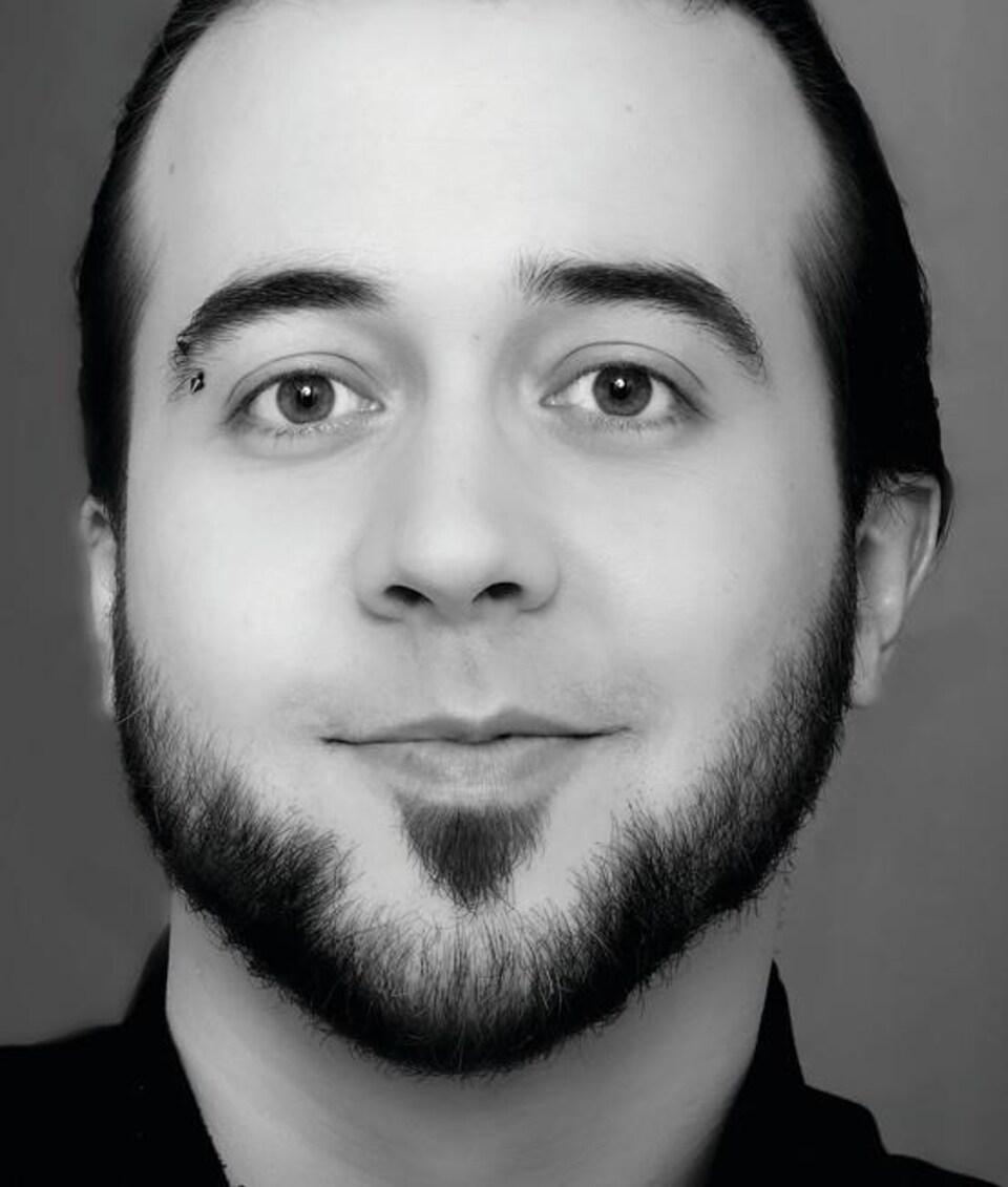 L'écrivain Bruno Massé. Il est jeune, début trentaine, cheveux bruns, petite barbe taillée et regard pétillant. Il a une boucle d,oreille dans le sourcil.
