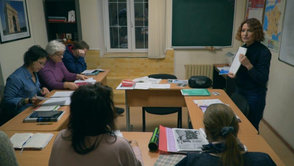 Une femme tient un document dans ses mains devant quelques personnes assis en rond dans une petite classe.