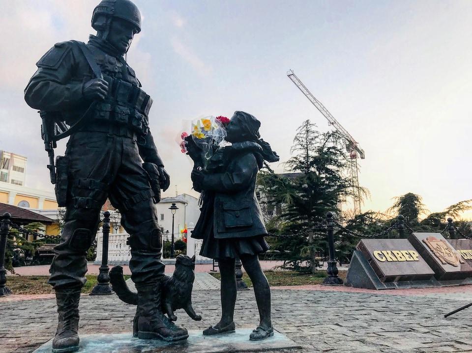 Trois statues en bronze représentent un soldat avec son arme dans le dos regardant une petite fille lui tendant un bouquet de fleurs. À leurs pieds on peut voir un chat aussi en bronze.