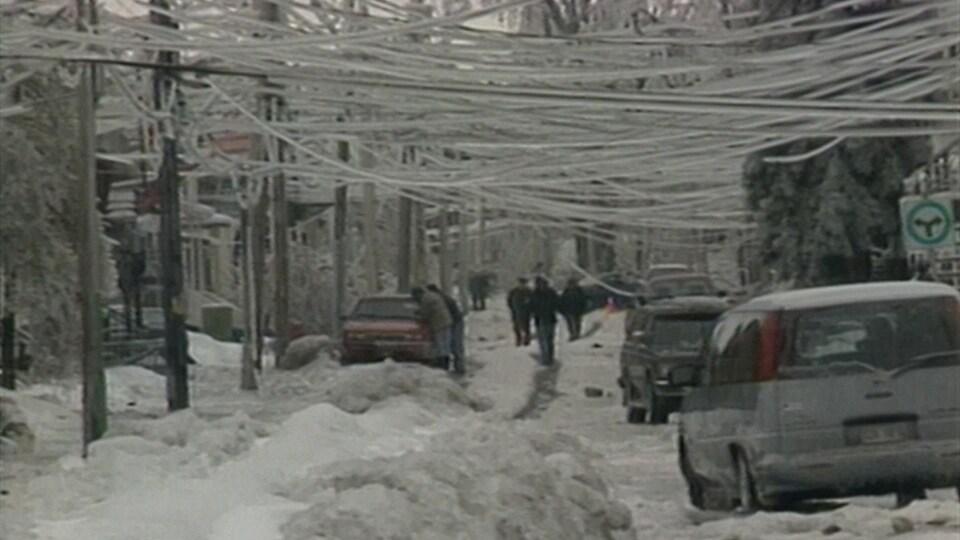 Des fils électriques couverts de glace pendent dangereusement à quelques mètres au-dessus de la rue à Montréal.