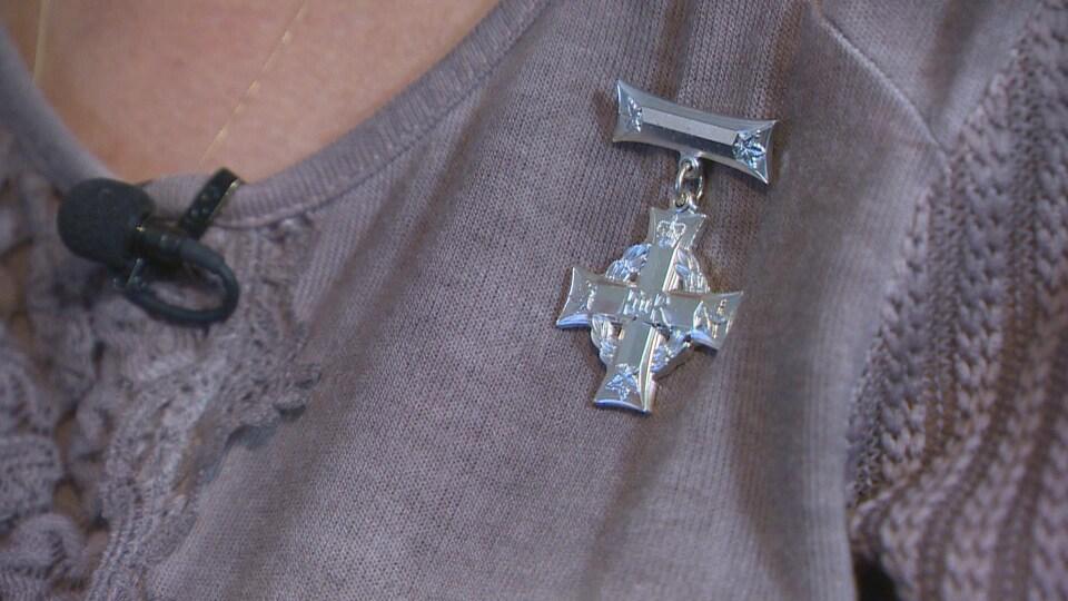 Une médaille formée d'une croix et d'une couronne de laurier d'argent est épinglé à un chandail mauve.