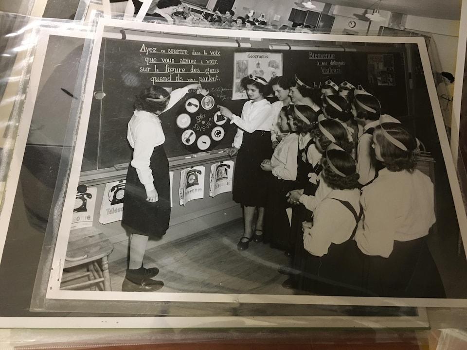 Les élèves reçoivent des cours pour apprendre à utiliser la nouvelle technologie que représente le téléphone à cadran dans les années 30.