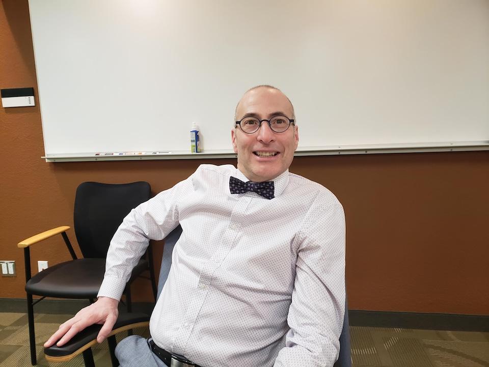 Un homme avec un noeud papillon et des lunettes rondes sourit.