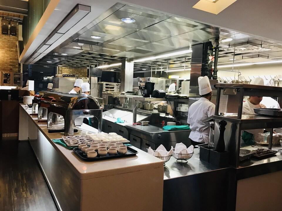 des cuisiniers préparent à manger dans une cuisine ouverte dans une café