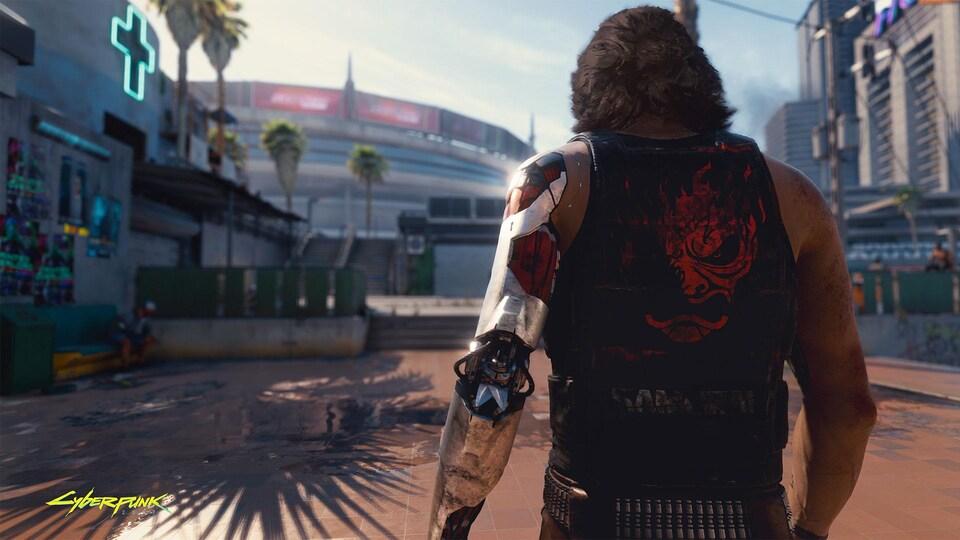 Un cyborg vu de dos regarde au loin dans une ville futuriste.
