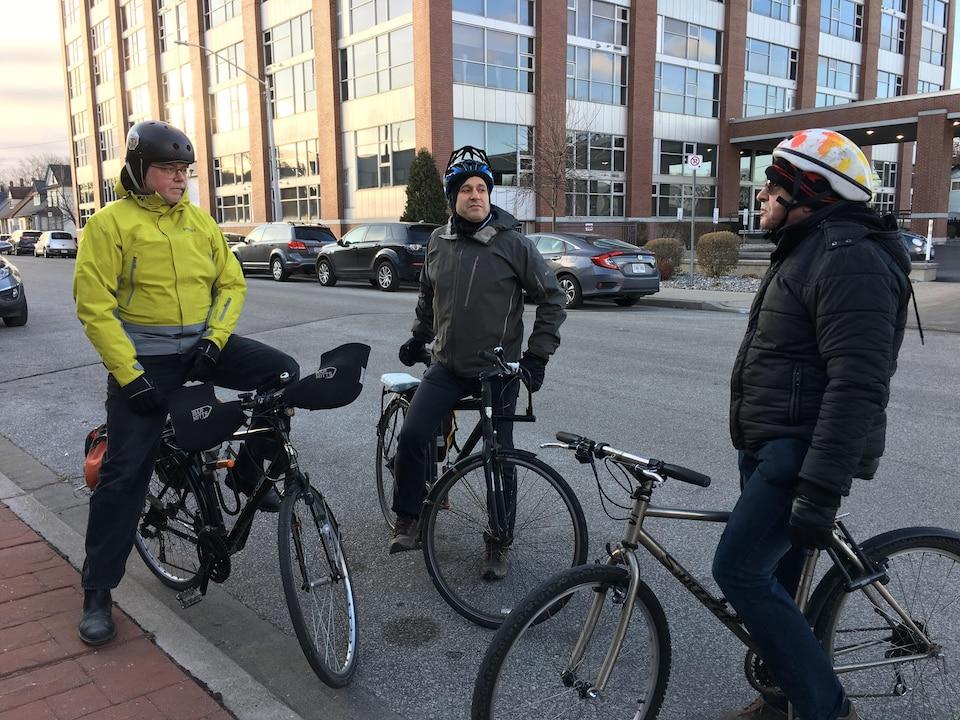 Trois cyclistes discutent.