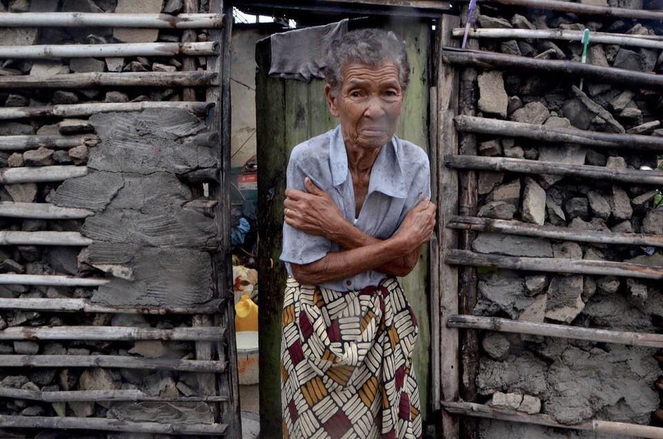 Une femme grelotte dans l'entrebaîllement de la porte de sa maison.