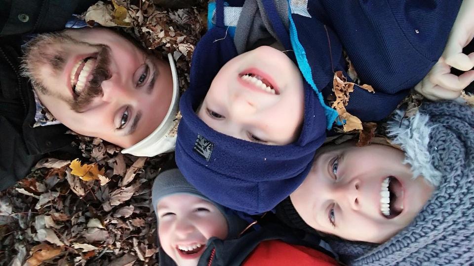 Deux adultes et deux enfants sourient dans un tas de feuilles mortes l'automne.