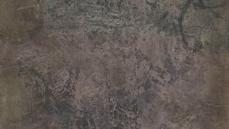 On voit la surface d'une plaque d'argent ternie.