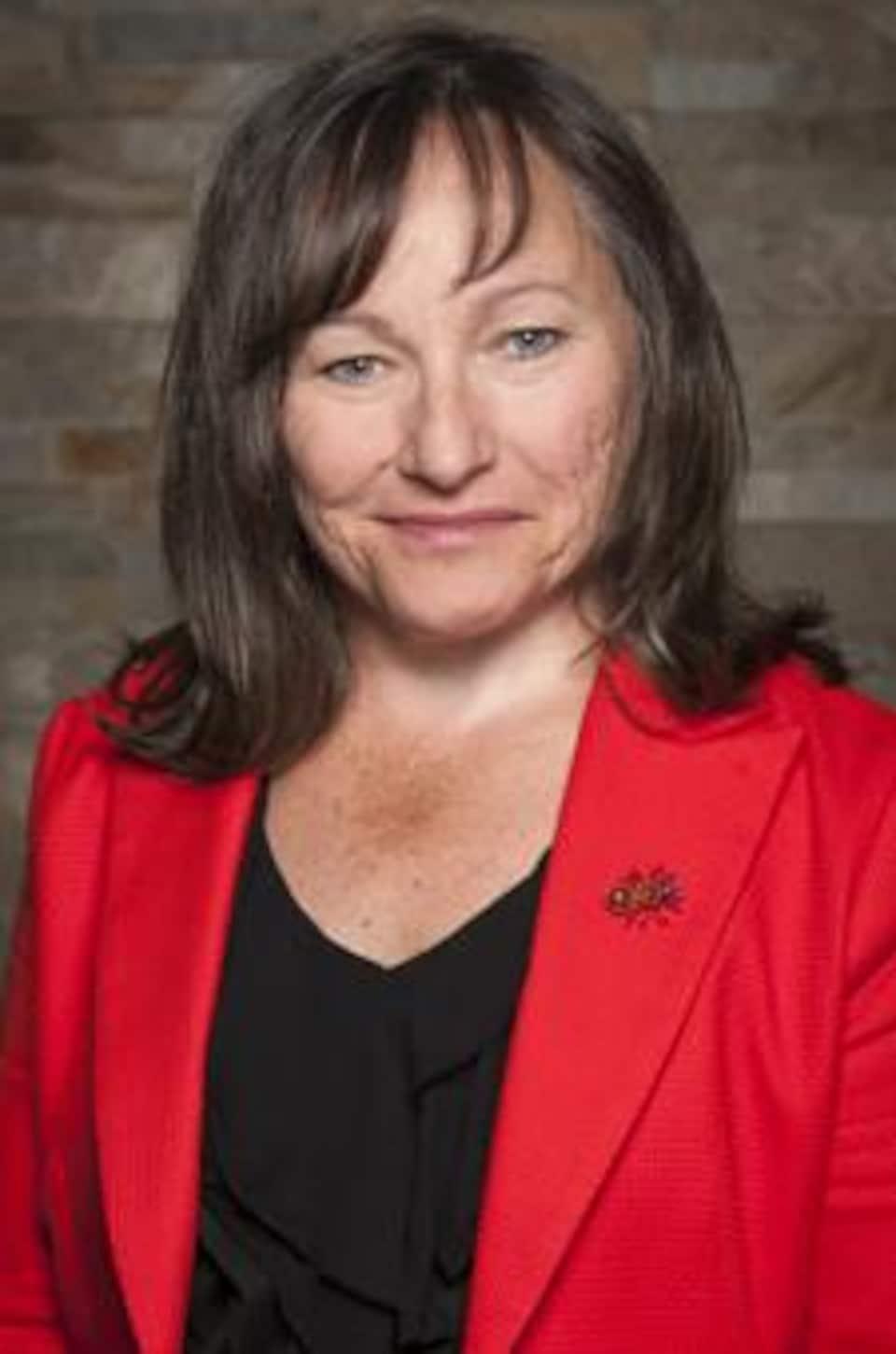 Une femme porte un veston rouge.