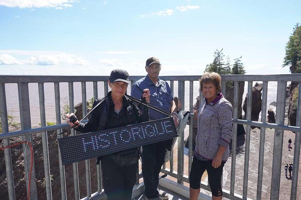 Visiteurs du site Hopewell Rocks tenant une pancarte lumineuse sur laquelle est inscrit le mot historique.