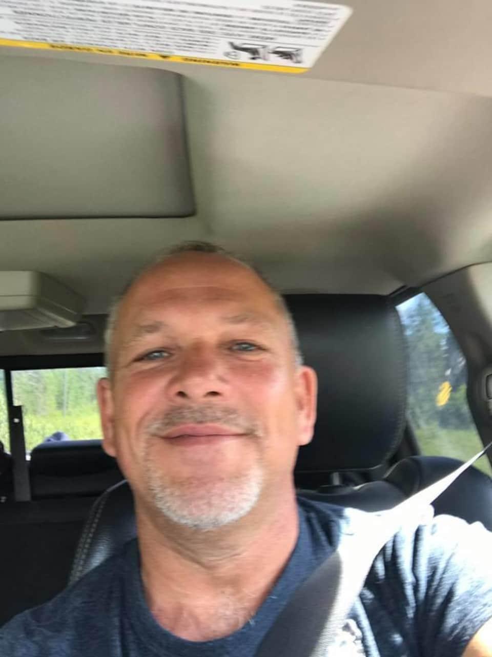 Égoportrait d'un homme dans un véhicule.
