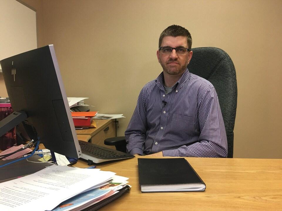 Daniel Gagnon assis à son bureau.