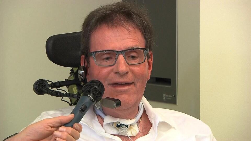 Un homme en chaise roulante parle au micro.