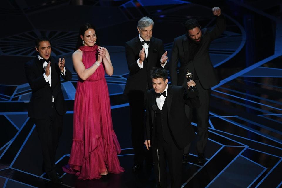Le réalisateur chilien Sebastián Lelio brandit son trophée sur la scène des Oscars 2018 tandis que quatre membres de son équipe l'applaudissent en arrière.