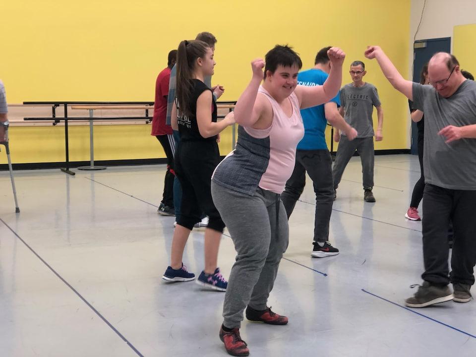 Stéphanie Tremblay danse les bras en l'air avec un grand sourire aux lèvres.