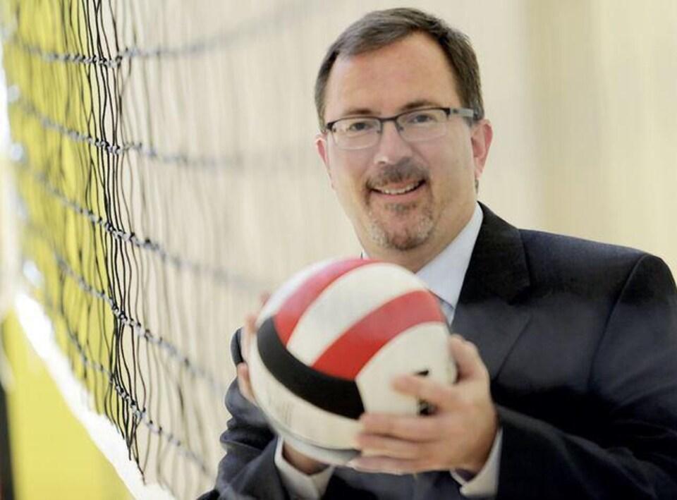 Un homme avec un costume noir et des lunettes qui tient un ballon dans ses mains au coeur d'un gymnase.