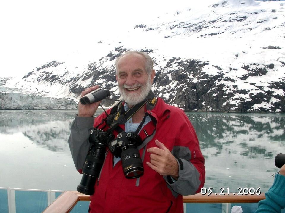 Un homme avec des appareils photos sourit à la caméra.