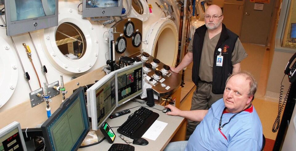 Le Docteur David Harrisson de l'Hôpital général de Vancouver, à côté d'une chambre hyperbare