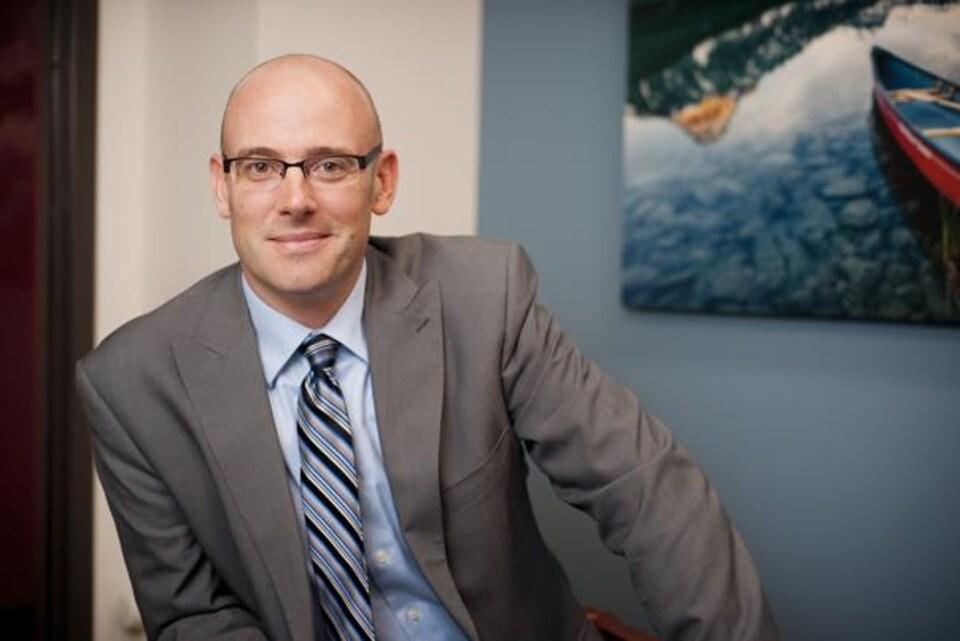Un homme qui semble chauve nous regarde droit dans les yeux en souriant. Il porte des lunettes et est vêtu d'un veston, d'une blouse et d'une cravate.