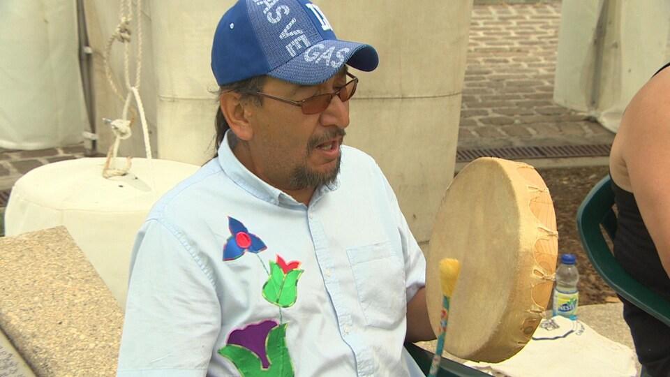 Un homme avec une casquette et des lunettes de soleil chante et joue du tambour.