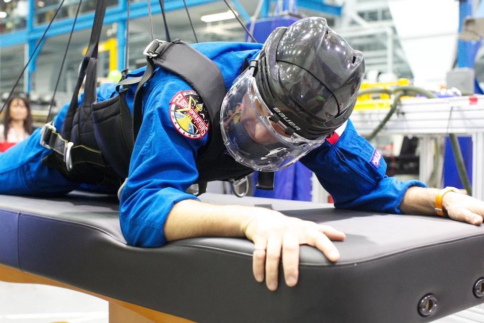 L'astronaute David Saint-Jacques porte un casque de hockey et s'agrippe à un matelas durant une simulation censée représenter les conditions de vie à la Station spatiale internationale.