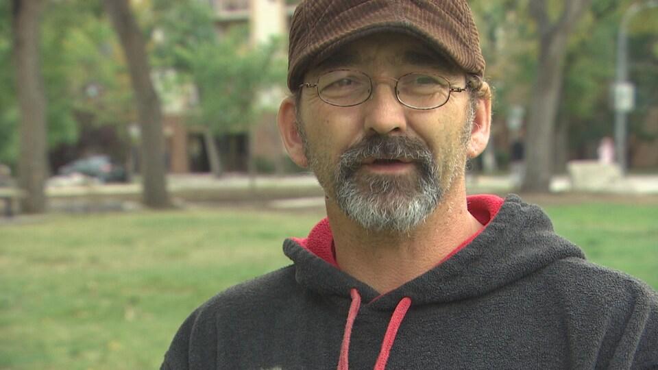 Un homme à l'air inquiet parle à la caméra, dans un parc.